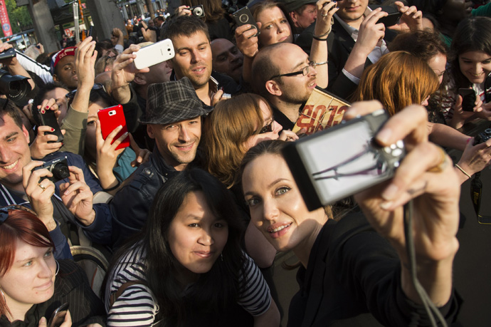"World War Z - Paris Premiere - Red Carpet ArrivalsPARIS, FRANCE - JUNE 03:  Angelina Jolie takes a photo of herself with a fan's camera as she poses with fans upon her arrival for the Paris premiere of ""World War Z"" at Cinema UGC Normandie on June 3, 2013"