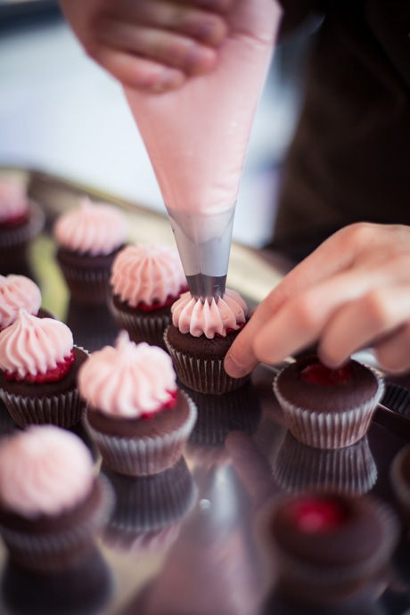 Finishing a cupcake with a topping - copyright Cupcake Affair