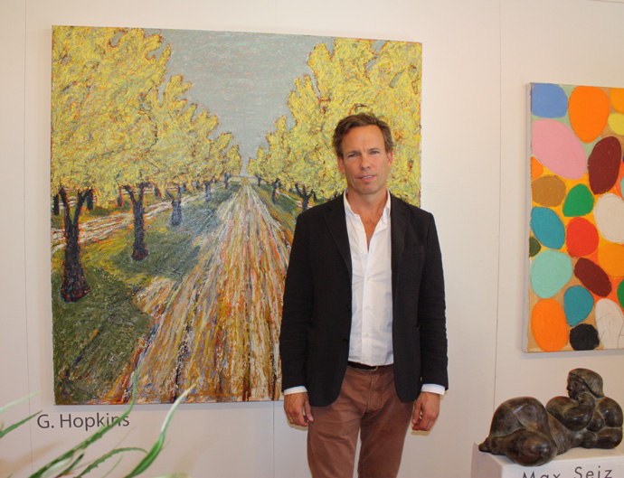 Gordon Hopkins in  front of his painting Orchard in the Luberon