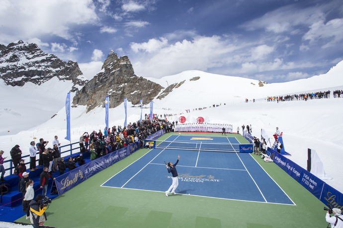 SWITZERLAND JUNGFRAUJOCH ROGER FEDERER LINDT Switzerland's champion tennis player Roger Federer and US champion ski racer Lindsey Vonn played an exhibition tennis match on the Aletsch Glacier below the Sphinx Summit to celebrate the opening of the LINDT Swiss Chocolate Heaven, a shop at 3,454 metres above sea level on Jungfraujoch, Switzerland, on Tuesday, July 16, 2014. The themed chocolate shop, which offers a wide range of the finest LINDT chocolate and the adjacent Master Chocolatiers parlor gives visitors a insight into how chocolate is made, was opened by Roger Federer and is collaboration between Swiss chocolate maker Lindt & Spruengli AG and Jungfrau Railway Holding AG. (PHOTOPRESS/Alexandra Wey)